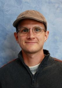 Headshot of Kyle Husmann with brown hat, glasses, white shirt, and gray jacket.